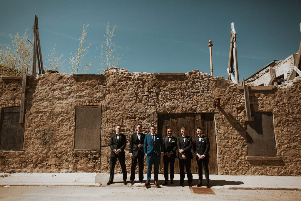 A groom and his groomsmen pose for a photo outside Elora Mill.