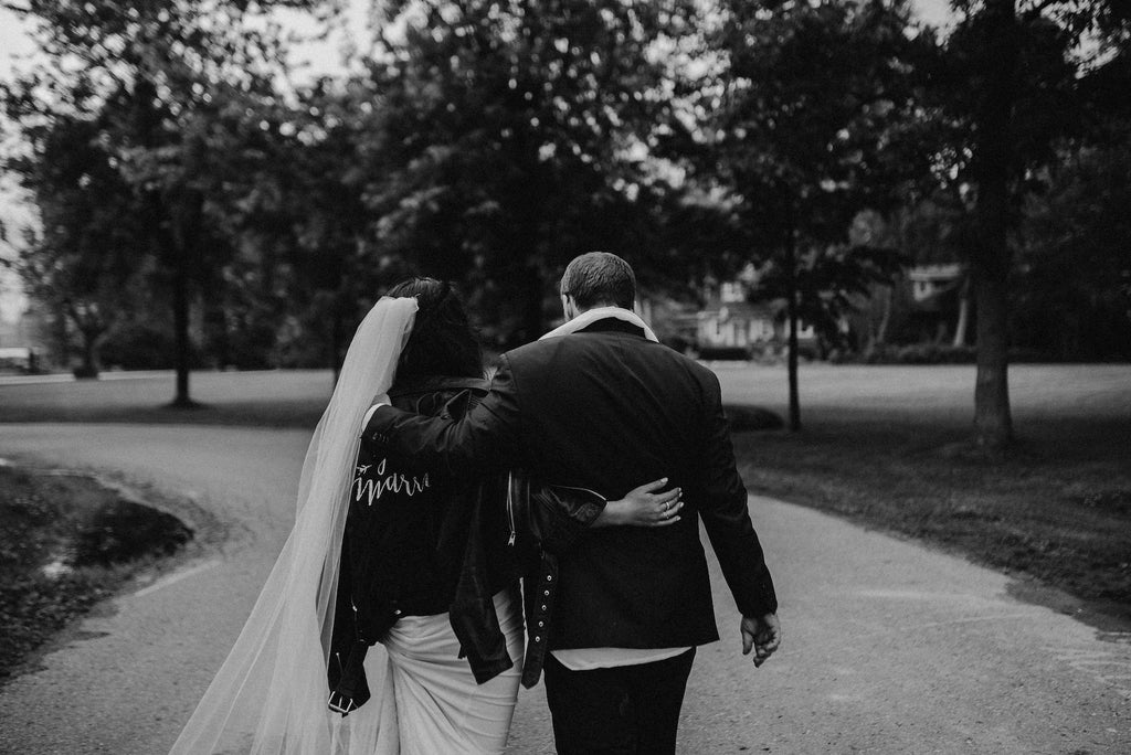 A newly web couple featuring a bride wearing #TheJustMarriedJacket.