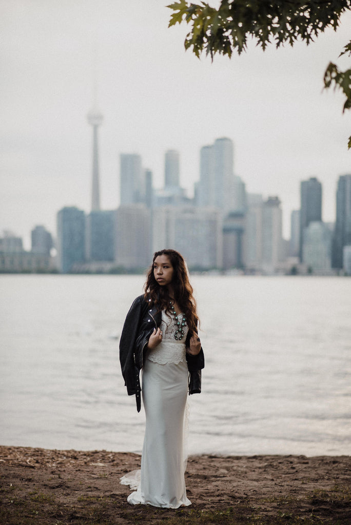 Boho bride wearing #TheJustMarriedJacket in front of the Toronto skyline.
