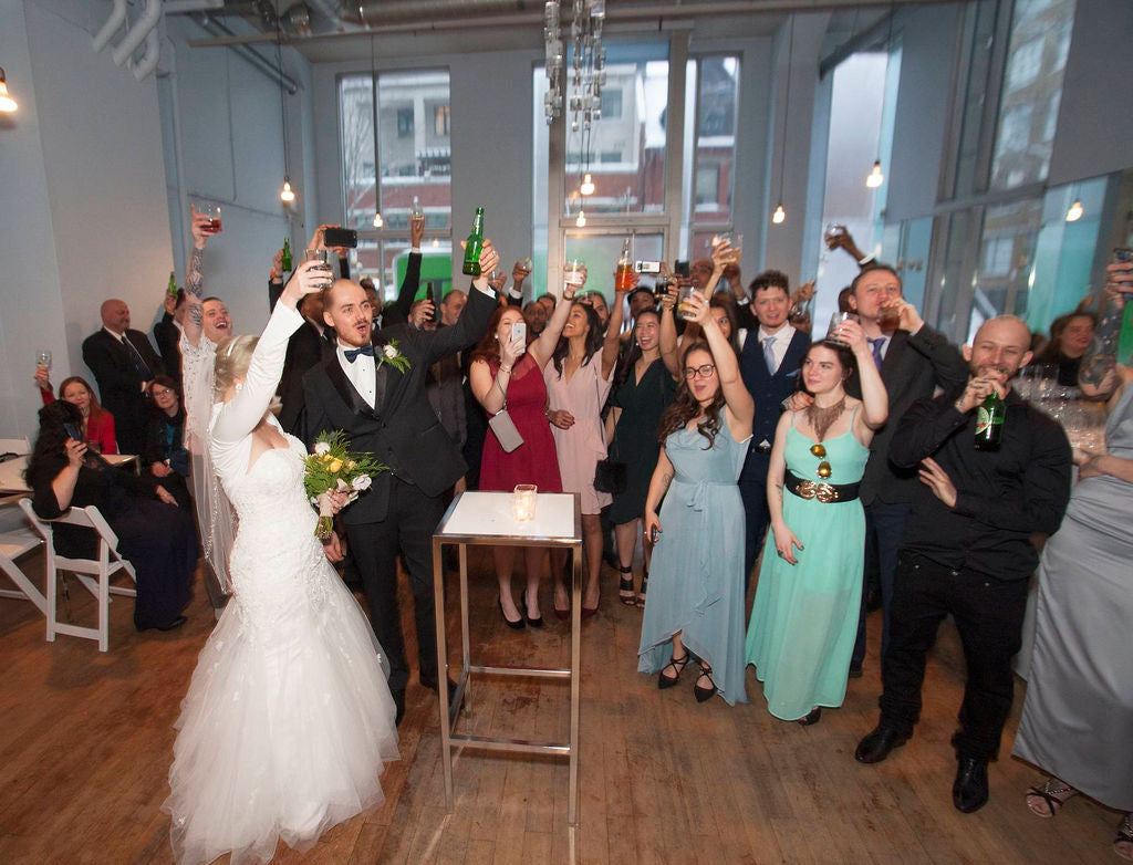 A happy newlywed couple toasts with their guests.