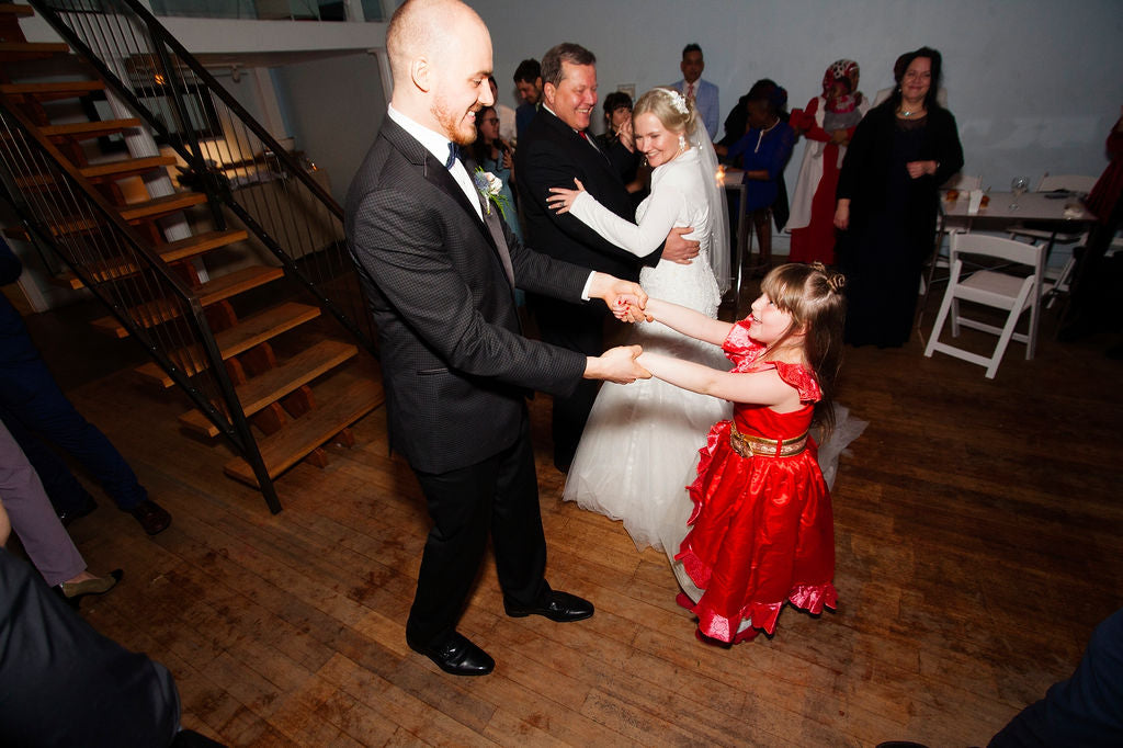 A newlywed groom dances with a little girl at his Toronto wedding.