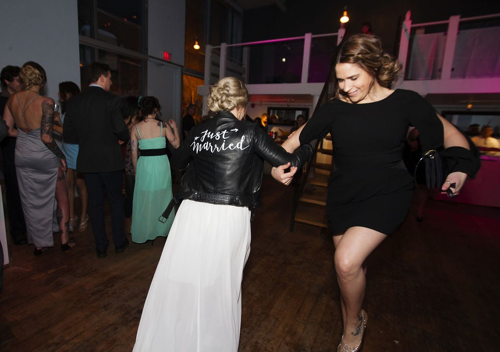 A newlywed bride dances with her friend on her wedding night.