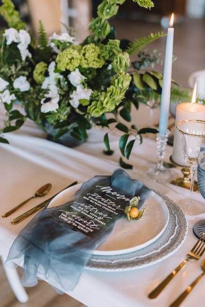Moody wedding table decor with moody teal hues and gold cutlery.
