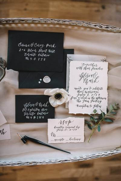 Black and white wedding stationary with calligraphy on it.