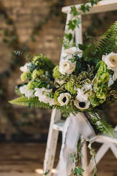 A beautiful wedding bouquet with lots of greens and white anemones.