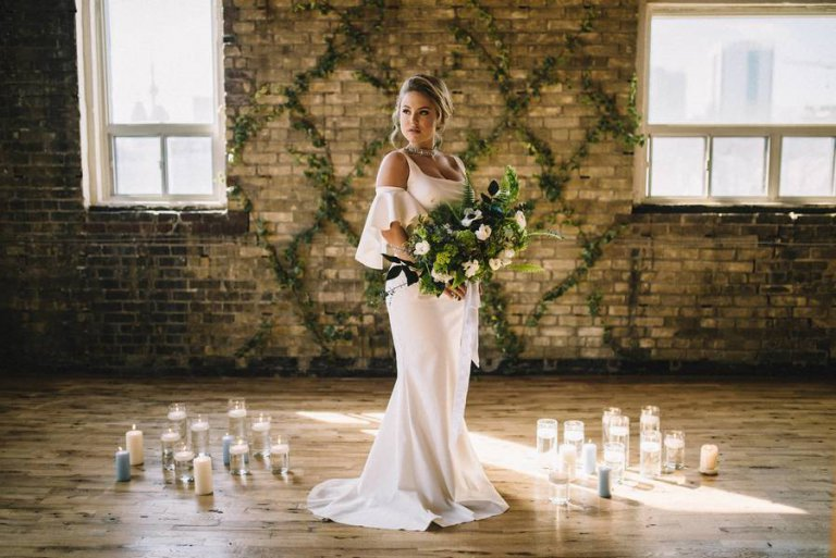 A beautiful bride posing against a brick wall with a stunning wedding bouquet.