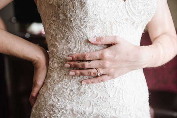 Delicate details on the bride's outfit including a vintage, lace dress and a stunning engagement ring.
