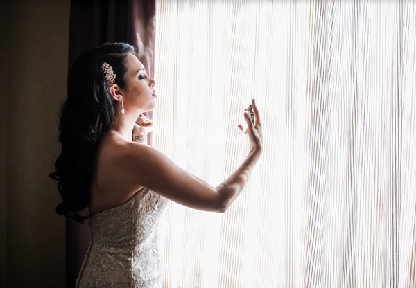 A bride sprays on her favorite perfume in preparation for her big day.