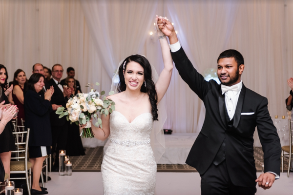 A bride and groom raise their hands after sharing a kiss and walking down the aisle.