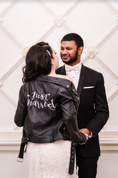 The bride shows off her Just Married Jacket with her new husband.