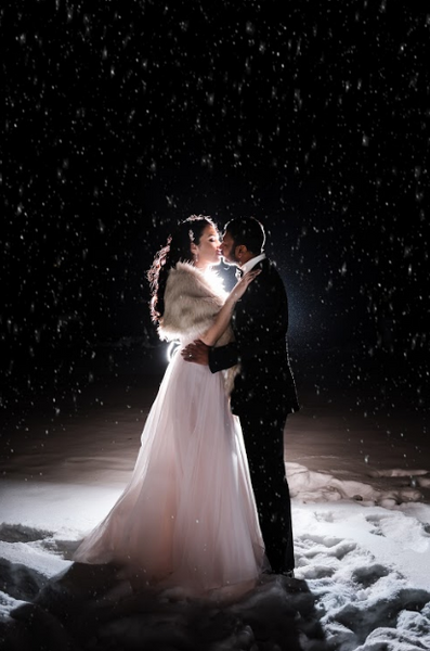 The bride and groom share a kiss at night at a glamorous Toronto winter wedding.