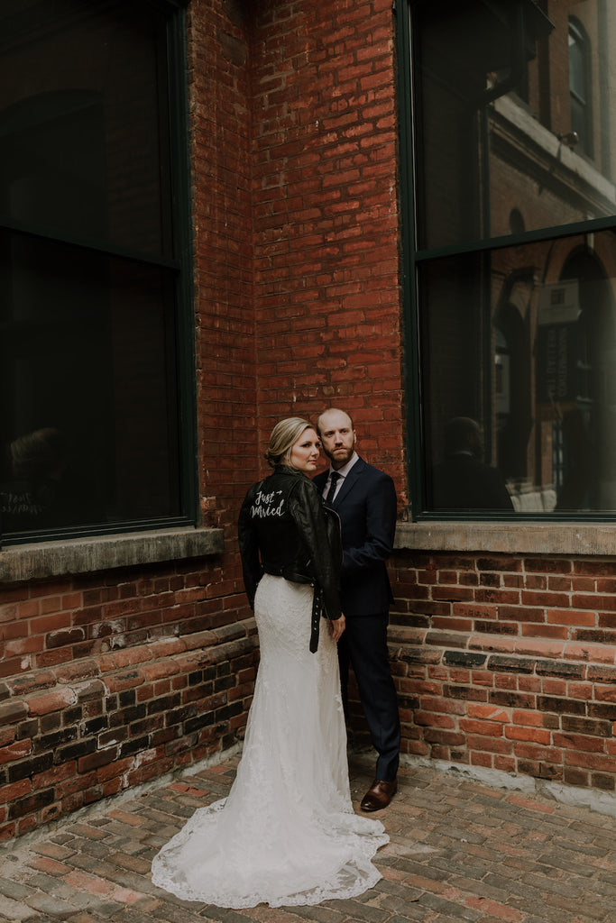 Newlyweds posing for a photo outside Archeo in Toronto's distillery district.