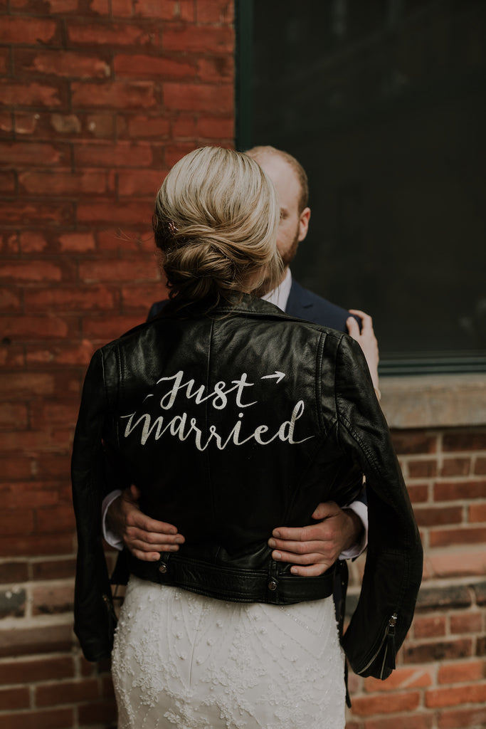 A bride with blonde hair in a stylish updo wearing a leather jacket.