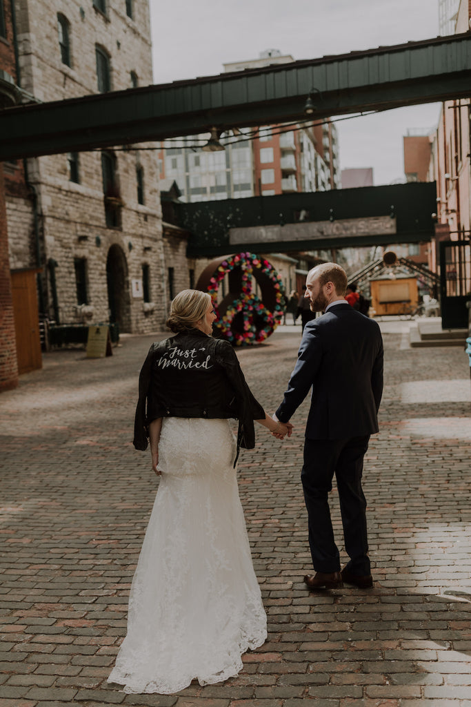 A newlywed couple poses for a photo in Toronto's distillery district.
