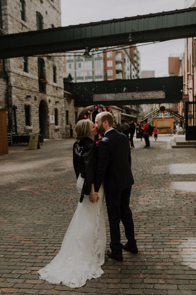 A bride and groom share a kiss after tying the knot in Toronto's distillery district.