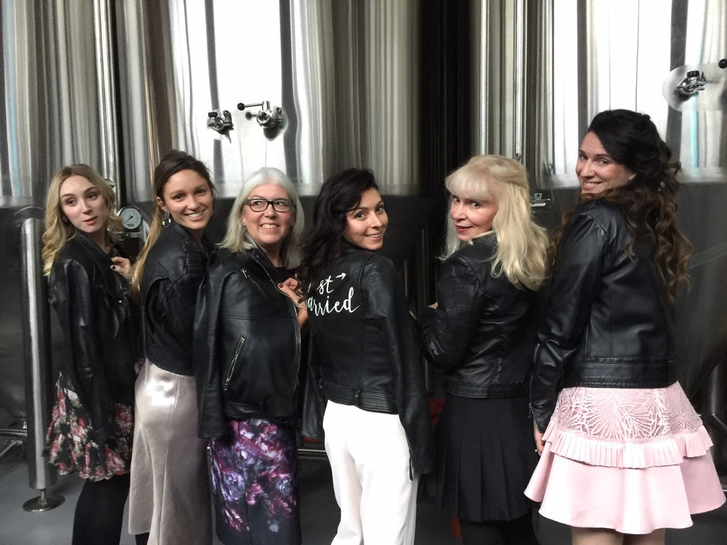 A bride and her friends show off their matching leather jackets on her big day.