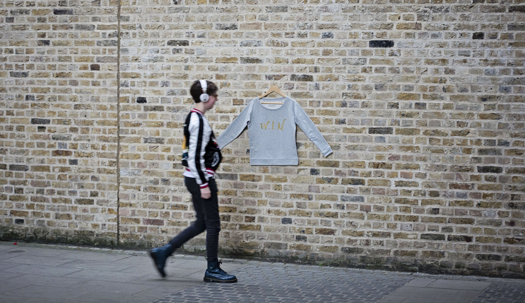 Sweatshirt hanging on a wall with passer by walking in front of it.