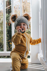 Baby kneeling on porch wearing an organic cotton footie pajama in honey with a grey knit cap that has honey colored pompoms on top.