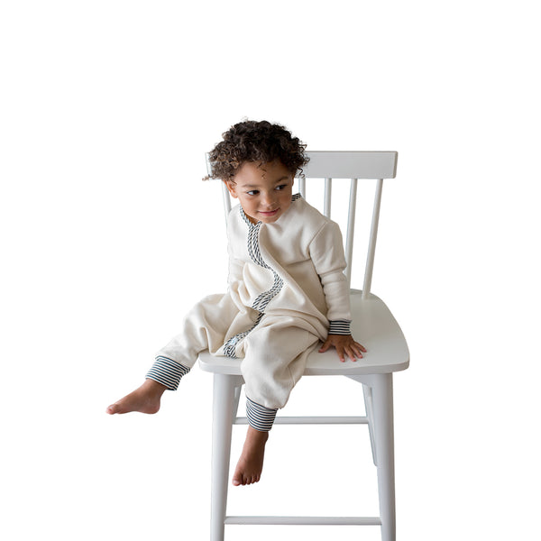 Child in sleeper bag sitting on a chair
