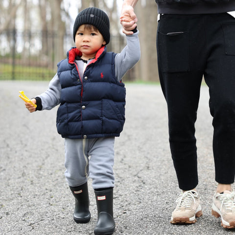 Boy walking next to parents, holding hands. Wearing a grey cotton fleece romper with rubber boots, down vest  and a knit cap.