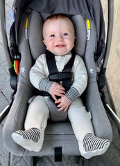Baby in car seat wearing a organic cotton fleece footie in natural with grey and natural striped trim at cuffs and toes
