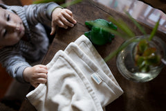 baby reaching for organic cotton velour lovey on table. Lovey is all natural with a green rubber frog sitting next to it