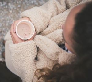 View from above of girl holding cup wearing a natural colored sherpa fleece jacket