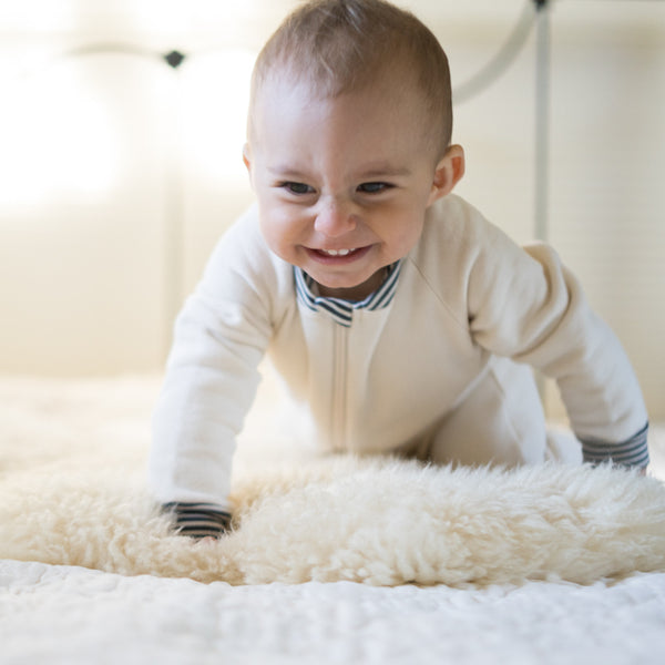 Picture of baby crawling towards the camera. Baby is wearing a CastleWare Baby footed pajama in natural fleece with grey and natural striped contrast trim at the neckband and cuffs.