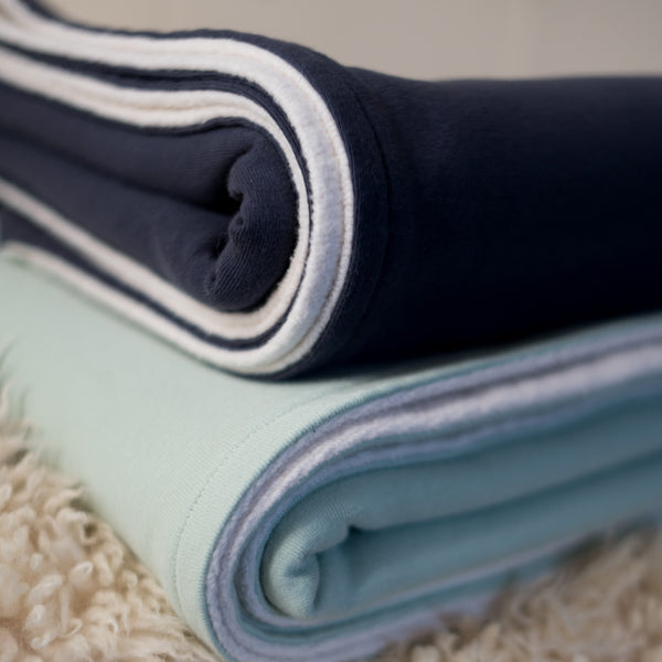Stack of two toddler blankets. Bottom blanket is mint green and natural. Top blanket is denim blue and natural.