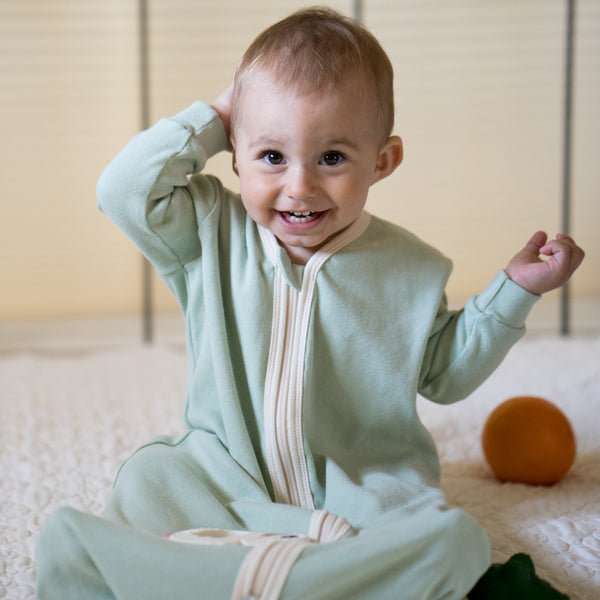 Baby is sitting up and smiling at the camera. Baby is wearing a CastleWare Baby long sleeve sleeper bag/wearable blanket in mint green with natural trim binding. Sleep sack has long sleeves.