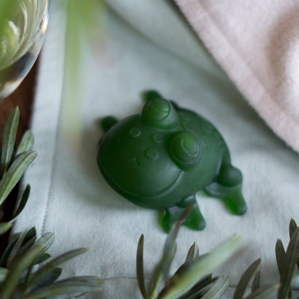 Green Hevea toy frog made with natural rubber in green. Frog is smiling towards the camera and is sitting on top of a mint green CastleWare Baby cotton fleece blanket for toddlers.