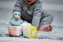 baby sitting and leaning forward to play with his Hevea rubber duck and blocks. Hevea duck is mint green, baby is wearing a charcoal grey striped pajama set
