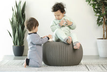 toddler sitting on bean bag wearing a mint colored fleece footie with charcoal grey striped trim. Baby kneeling next to her wearing a grey fleece footie with black trim.