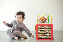 toddler wearing a mushroom colored romper with a natural zipper down the front. smiling at the camera and playing with a stacking toy set.