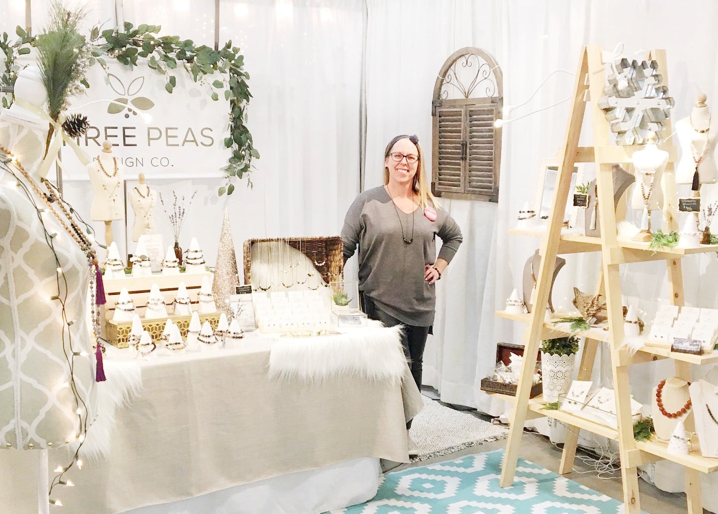 Carrie standing in the middle of her booth display at the Niagara Handmade Market