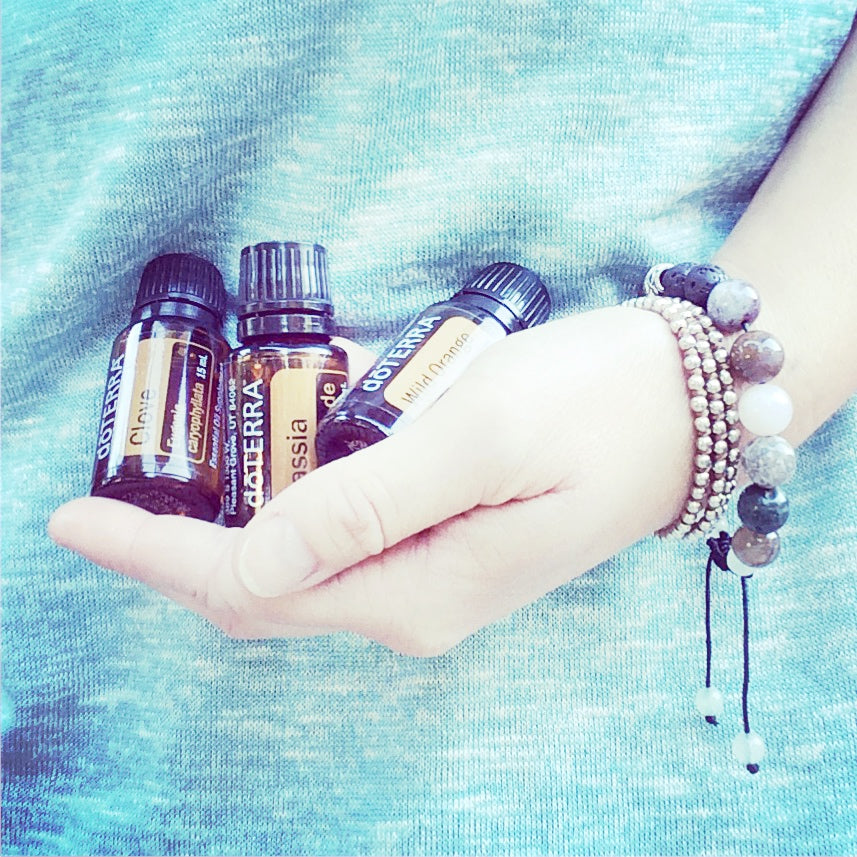 hand holding 3 bottles of Doterra essential oils and wearing stack of beaded bracelets with blue background