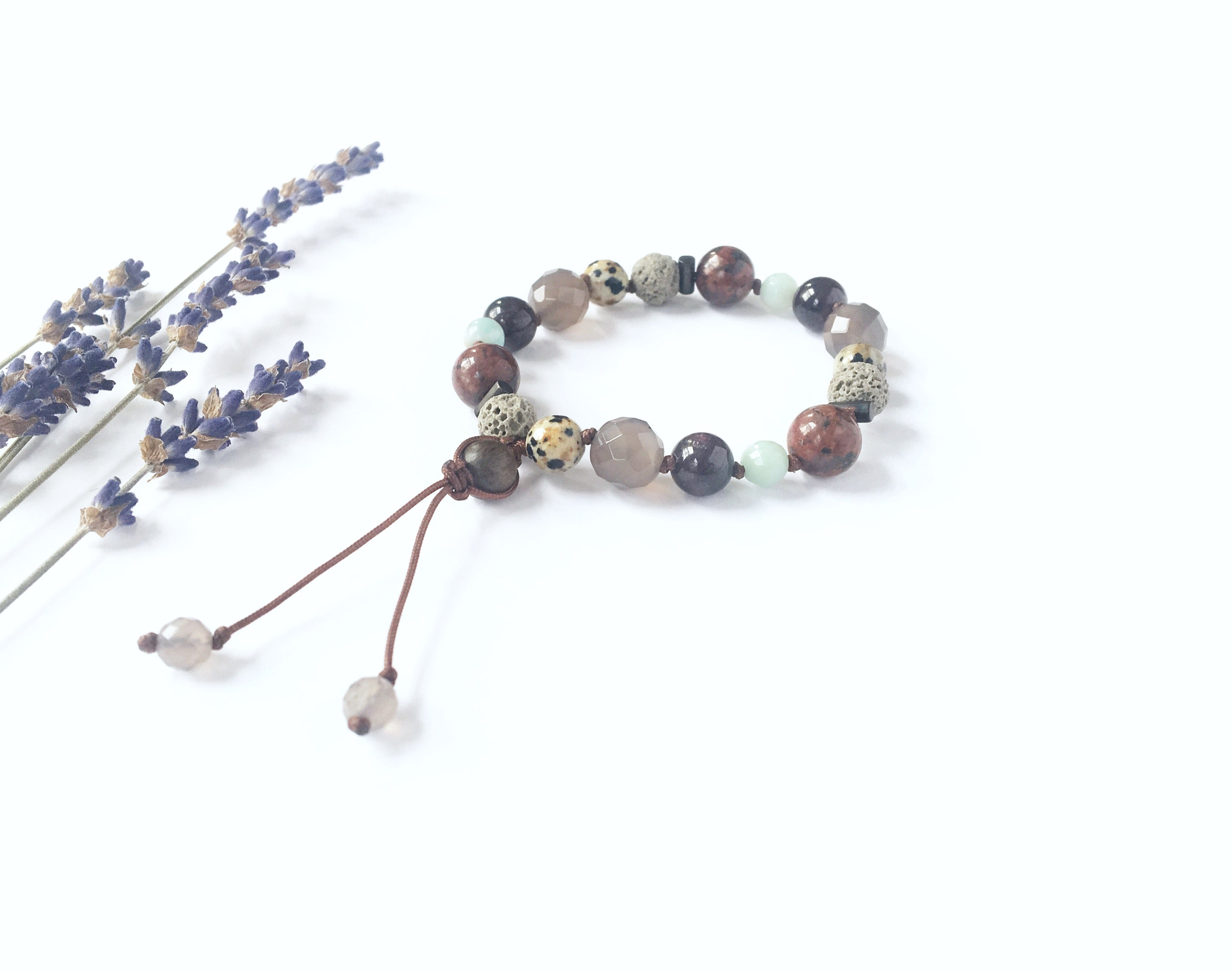 Gemstone and lava bead bracelet designed by Three Peas, alongside stems of dried lavender