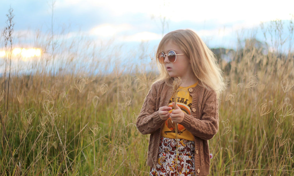 girl in field wearing oobi caramel brown winter cardigan