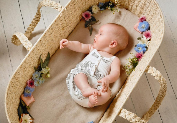 baby girl in a basket wearing wilson & frenchy baby playsuit neutral wonderful print
