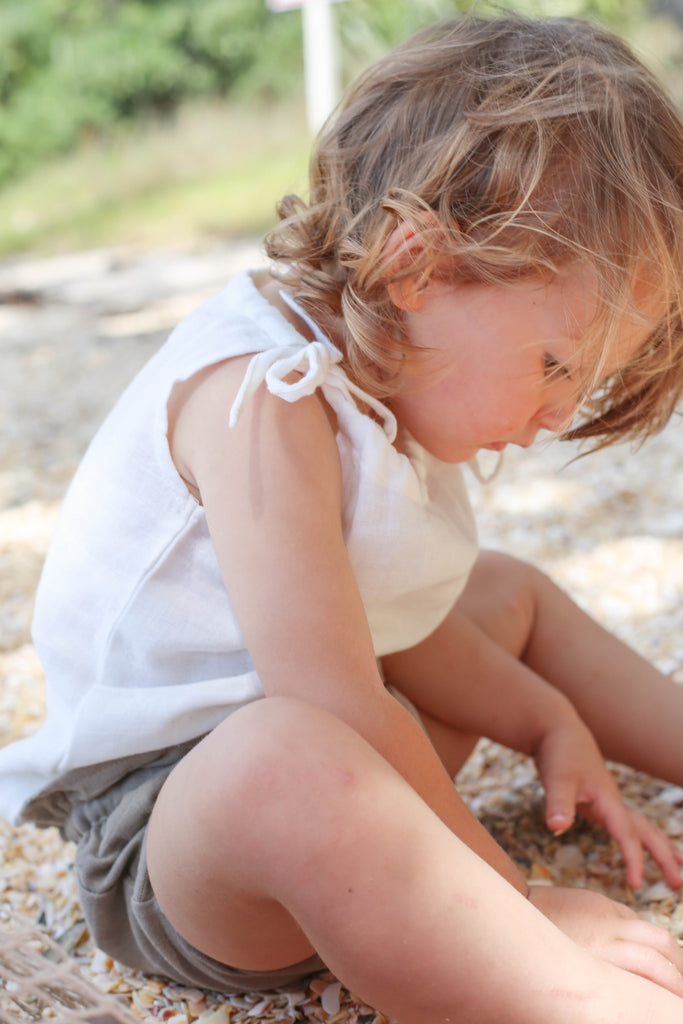 girl playing in sand wearing le edit marni singlet blanc