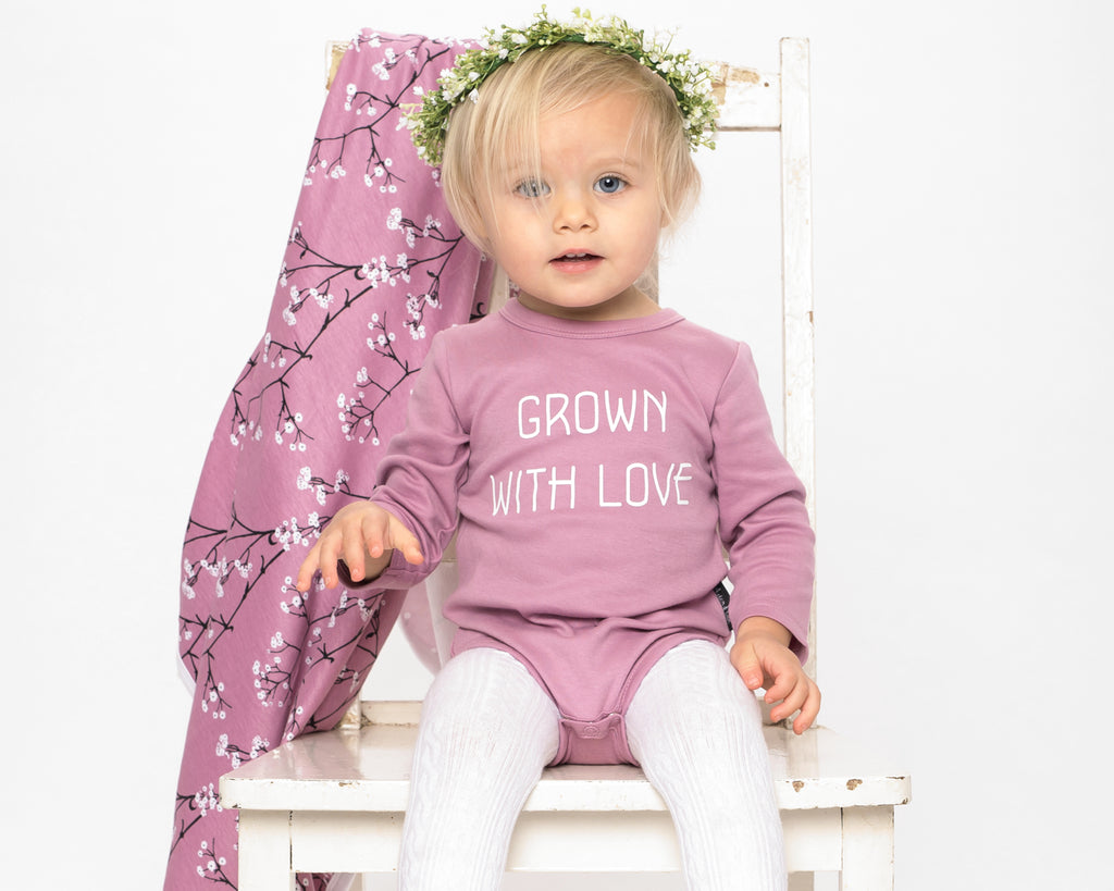 baby on chair wearing aster and oak organic long sleeve onesie orchid colour