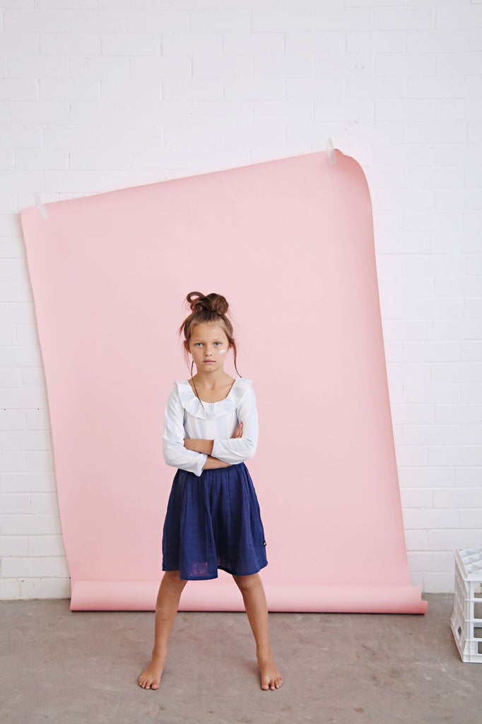 girl wearing anarkid block stripe long sleeve leotard and navy blue muslin skirt
