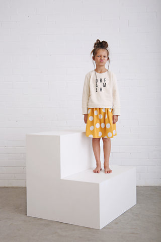 girl wearing girls and toddler white and yellow skirt with white spots