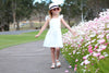 girl wearing swell and solis ruffle sleeve pinafore walking near flowers