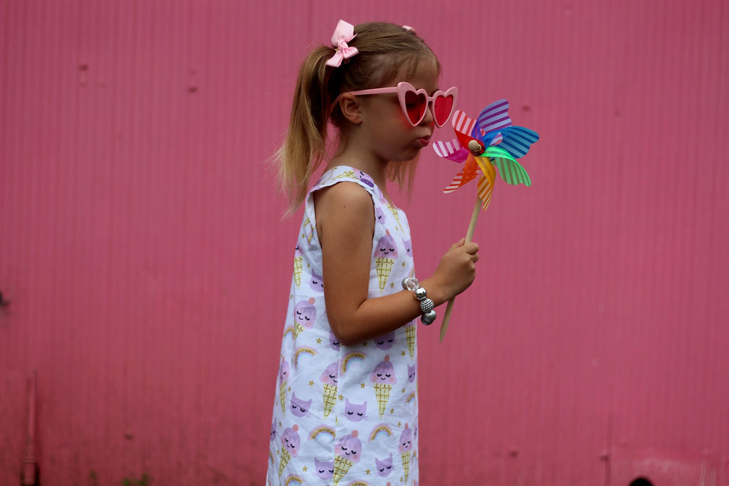 girl blowing rainbow windmill in the princess and the frock handmade girls tunic dress