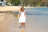 girl walking along the beach wearing ruffle sleeve white periwinkle pinafore by swell and solis