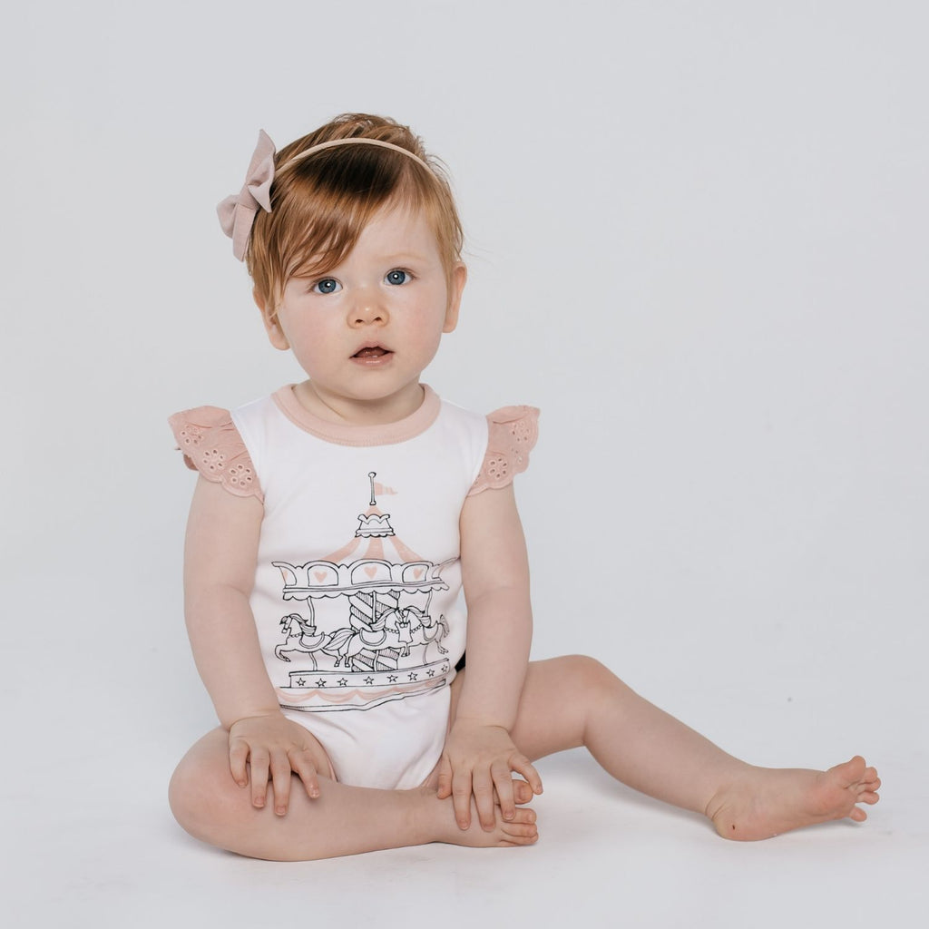baby girl wearing aster & oak's organic peach carousel romper