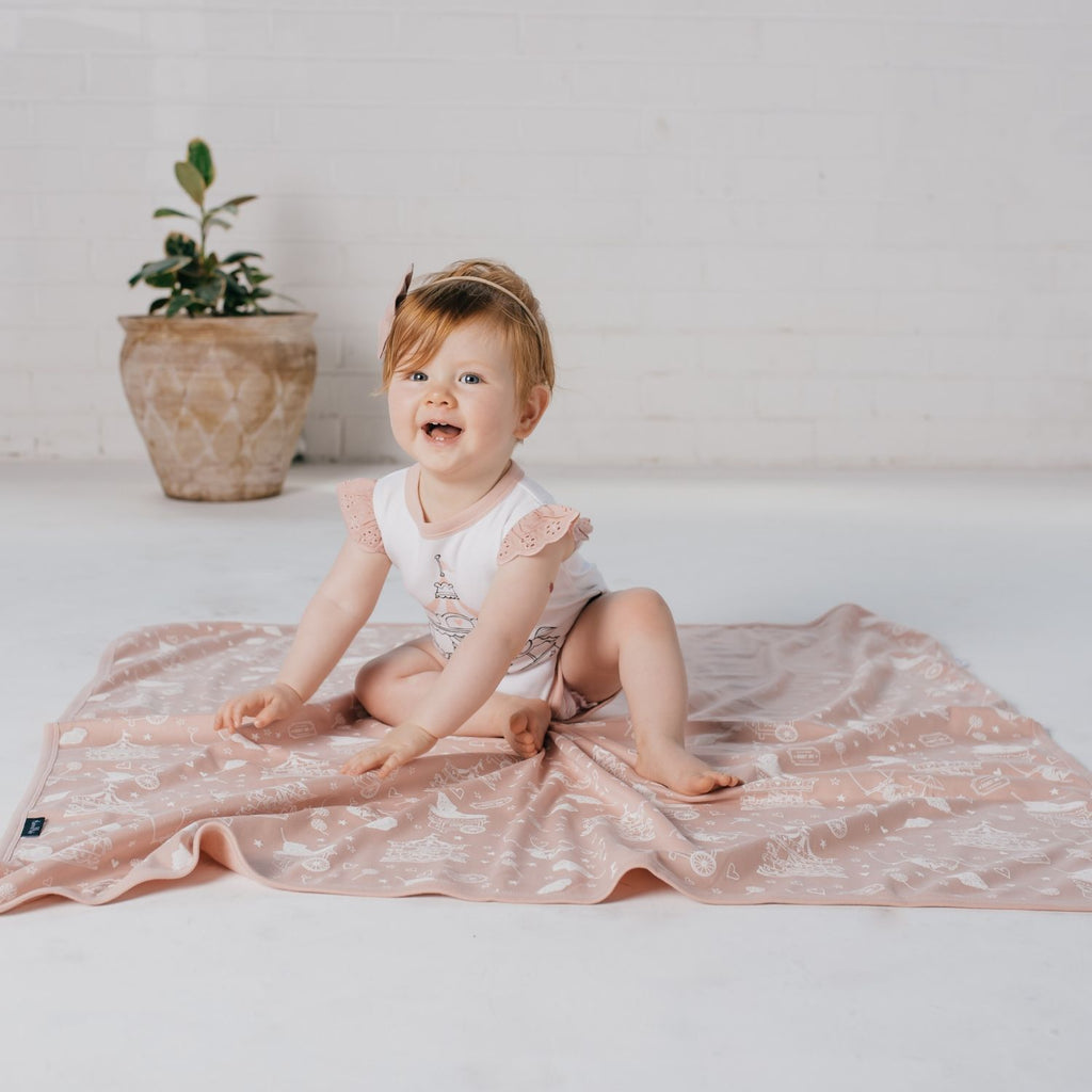 baby girl wearing organic baby romper with carousel drawing by aster & oak