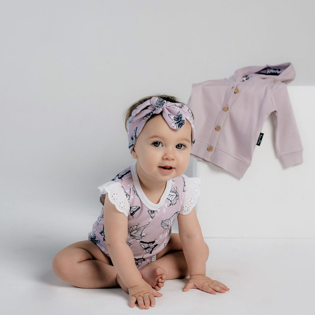 baby girl in lavender flutter sleeve romper by aster & oak
