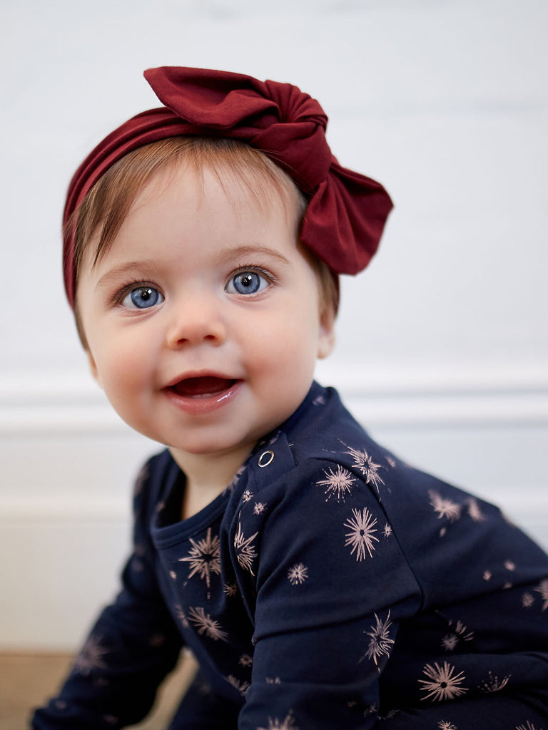 baby girl in navy romper with ruby headband